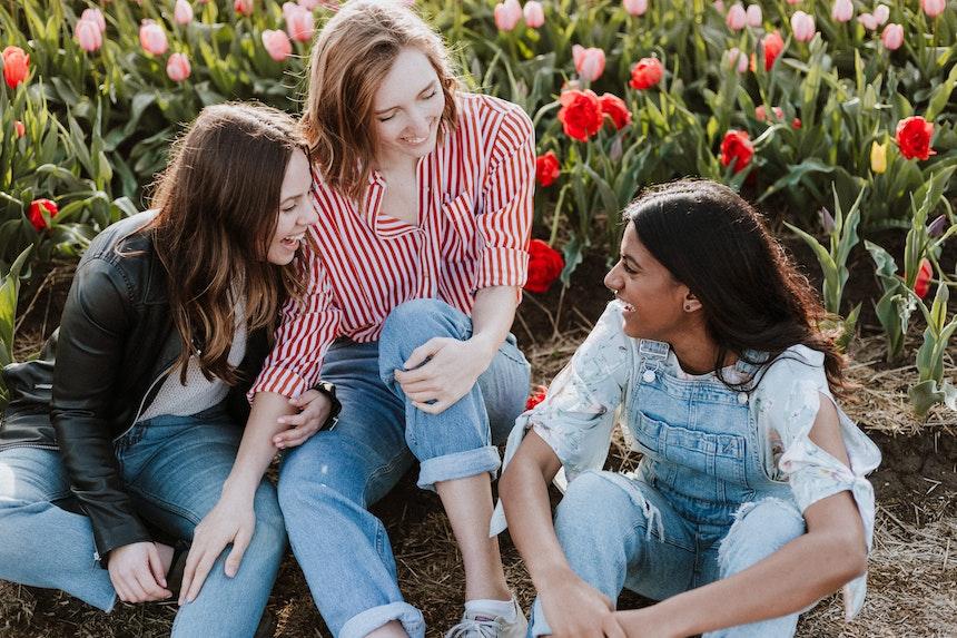 Three girls talking in a field.