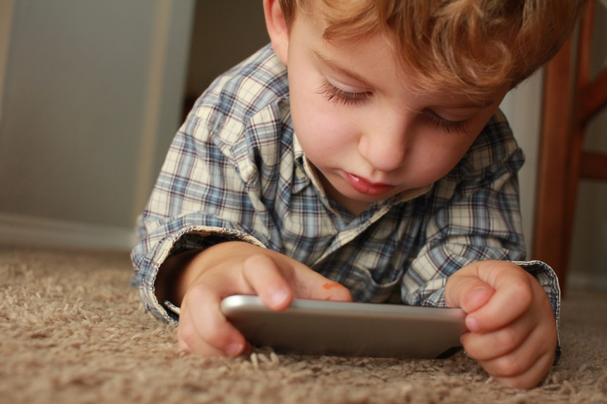 Little boy playing with a phone on the floor.