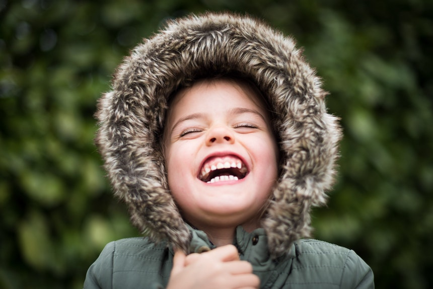 Boy laughing with his hood up.