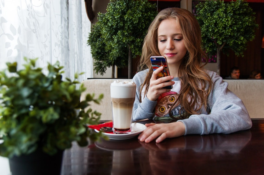 Girl on phone while drinking coffee.
