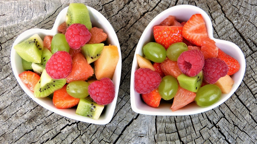 Two bowls of cut up fruit.