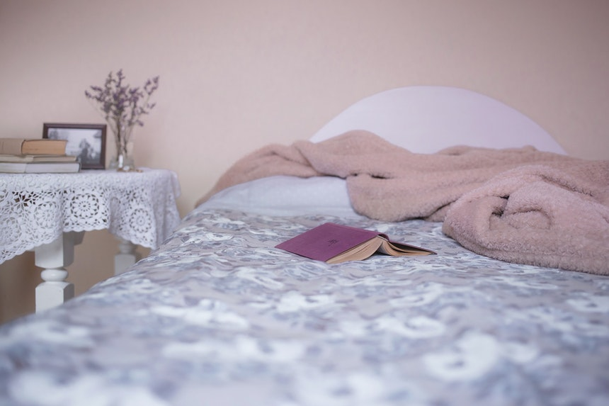 Book lying open on bed.