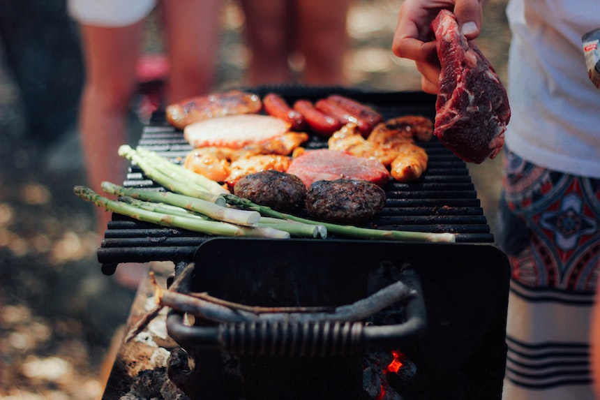 Barbecue with meat and vegetables cooking on it.
