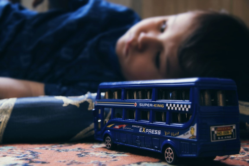 Sad child on the floor with a toy bus.
