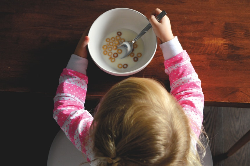 Child eating cereal at a wooden table.