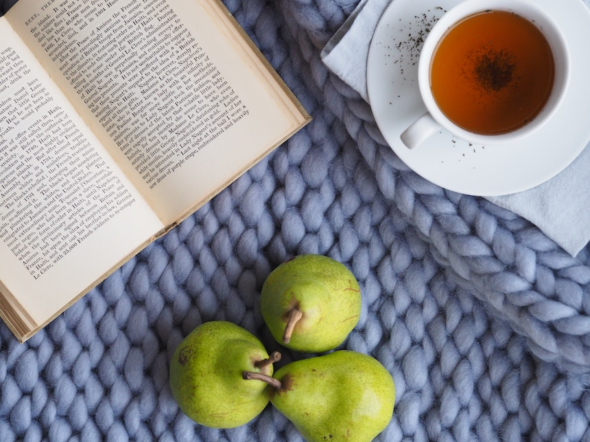 Pears next to a book and a cup of tea