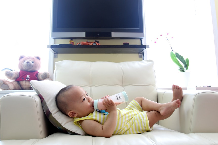 Baby lying on a couch drinking milk