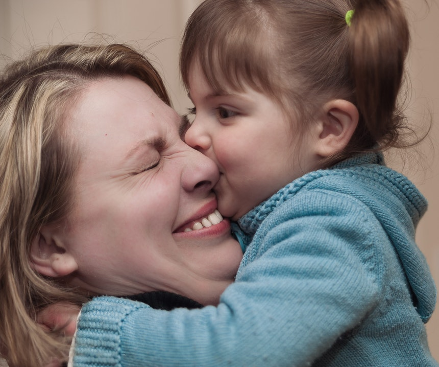 Toddler kissing mother on cheek