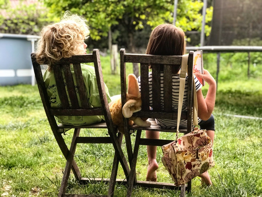 Two kids sitting on deck chairs