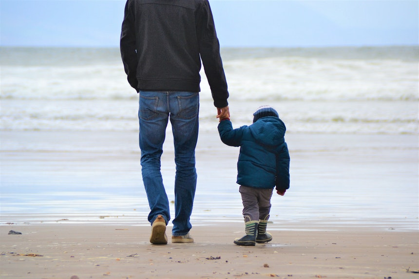 Father walking with son on the beach.