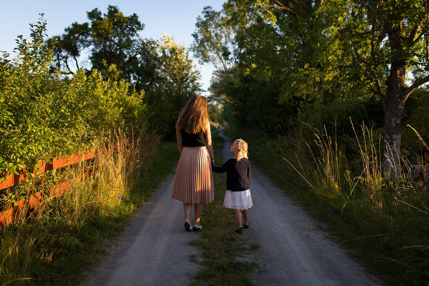 Parent and child walking down a country road.