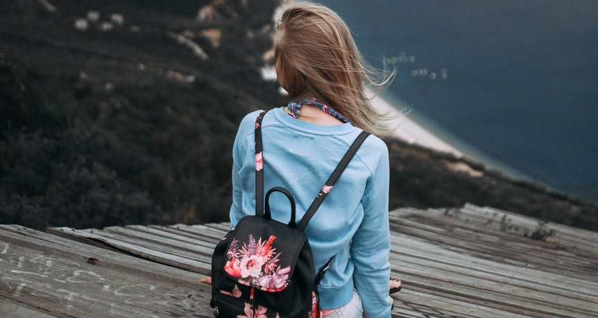 Girl alone beside a cliff.