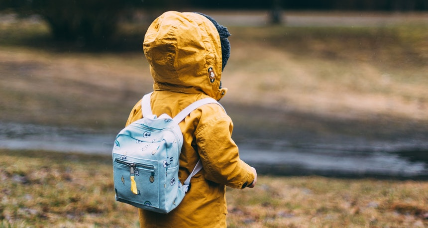 Child with yellow raincoat and schoolbag.
