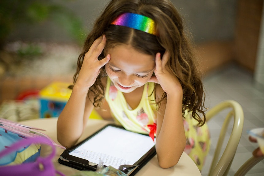 Little girl watching tablet.