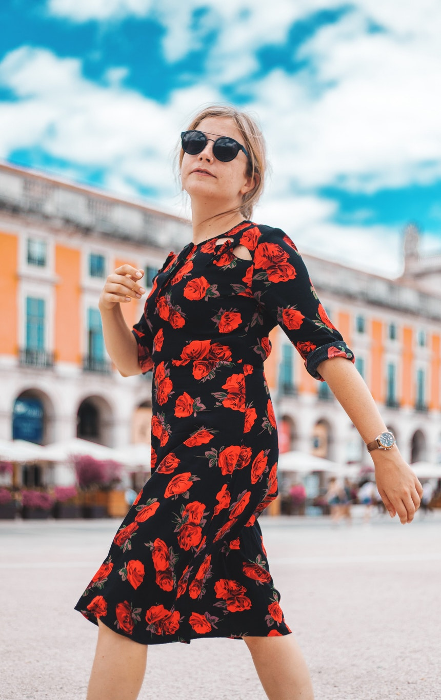 Woman walking in a black dress with red flowers.