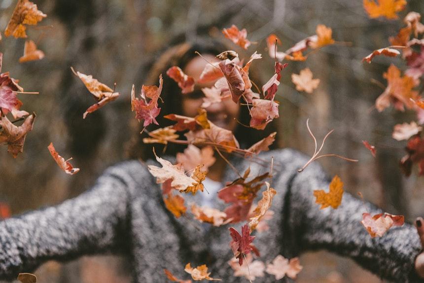 Girl throwing leaves.