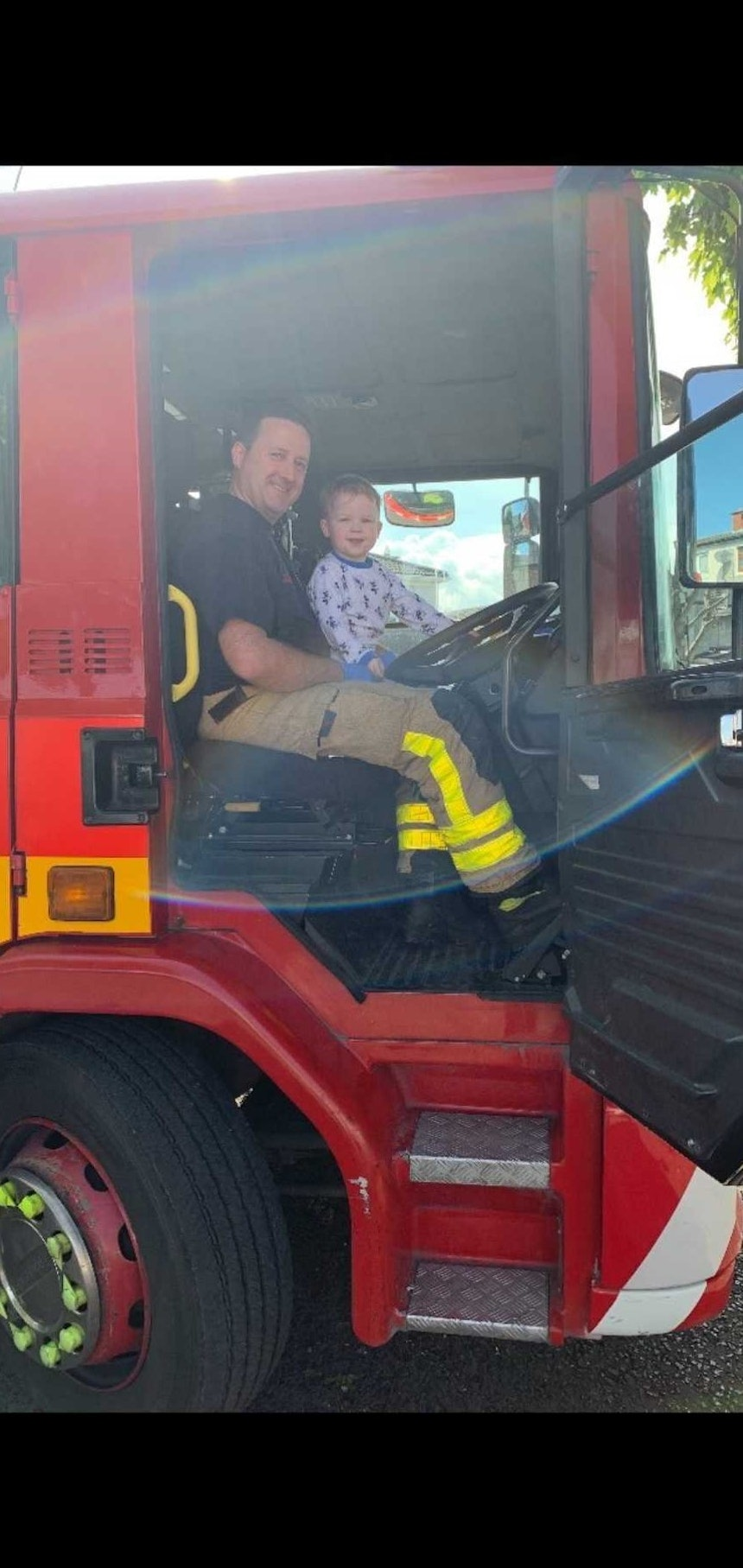 Little boy and fire fighter in a fire truck.