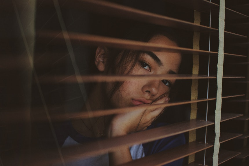 Girl behind blinds.