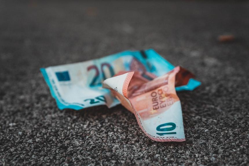 Crumpled euros on the ground.