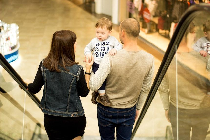Mum, dad and toddler on an escalator.