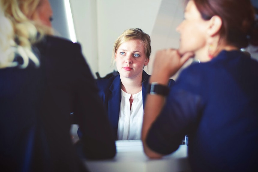 A woman in a meeting looking unhappy.