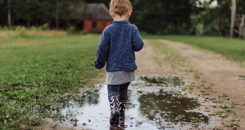 Boy walking in a puddle