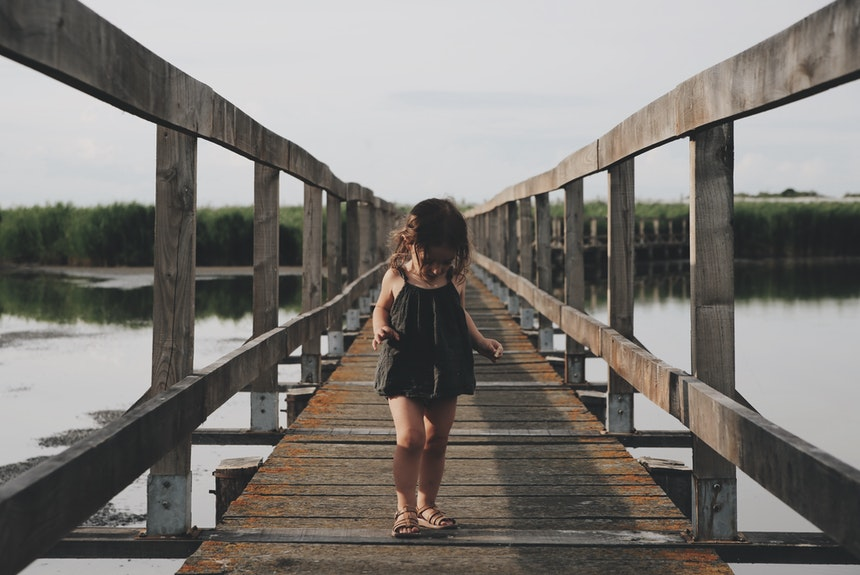 Little girl walking on a dock