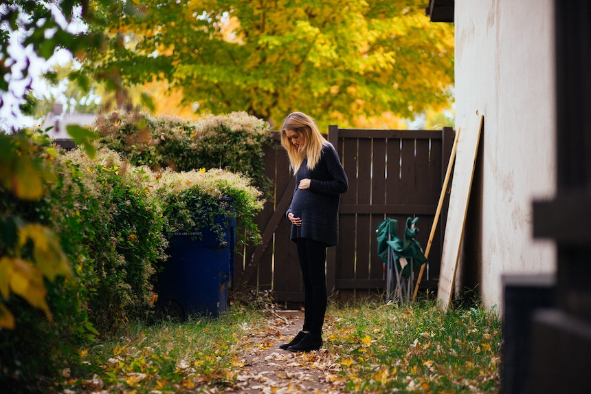 Pregnant woman standing in a garden