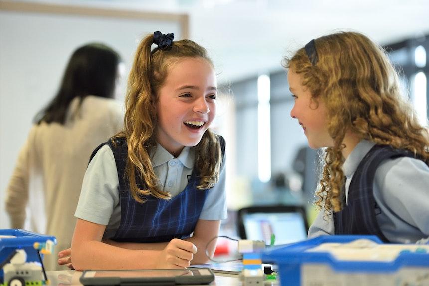 Two girls talking in school
